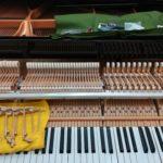 湿気が原因の動作不良のグランドピアノ部品を修理する様子